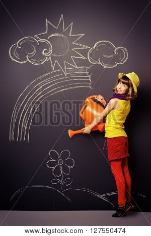 Joyful pretty girl in colorful clothes watering flowers drawn on a blackboard. Happy childhood.
