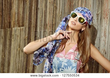 Beautiful romantic young woman in casual summer clothes stands by the old wooden fence. Outdoor fashion. Jeans style.