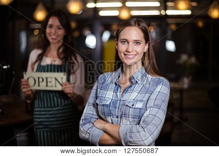 Smiling woman standing with arms crossed in the bar