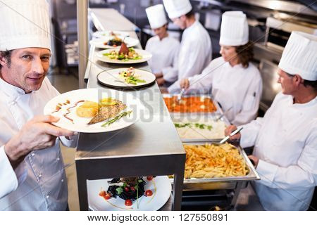 Portrait of chef handing dinner plates through order station in the commercial kitchen