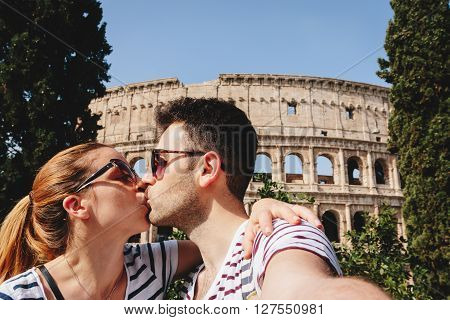 Young couple taking a selfie in Rome in front of the Colosseum
