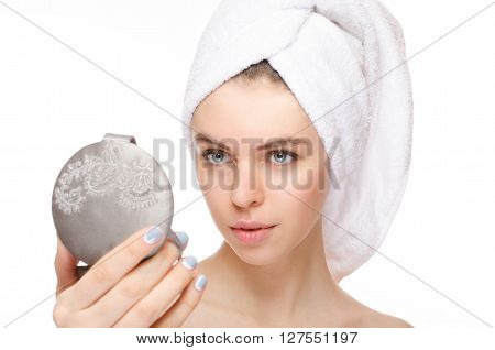 Portrait of beautiful girl touching with mirror with a towel on her head