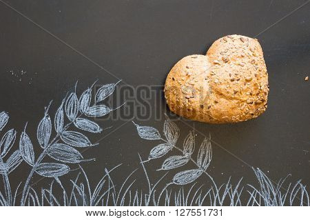 Heart shape of wholemeal bread on blackboard background