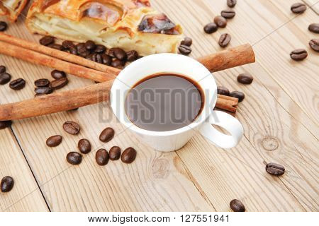 sweet round apple pie on wooden table with coffee cup and cinnamon sticks