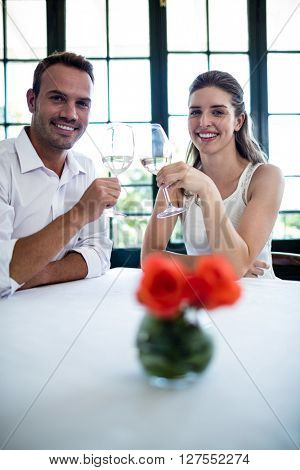 Portrait of couple toasting wine glasses at dining table in a restaurant