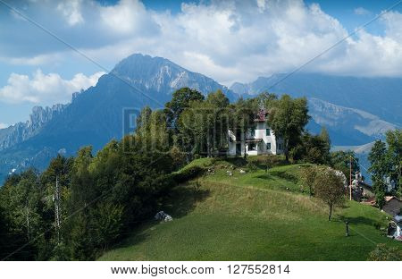 a white house on top of a hill at Piani d'Erna (part of the Alps) near Lake Como in Italy