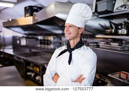 Happy male chef standing with arms crossed in commercial kitchen