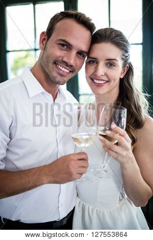 Portrait of couple toasting wine glasses in a restaurant