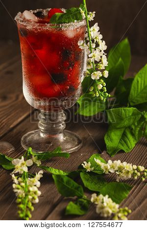 Berry Soft Drink With Ice On A Wooden Background And Flowers