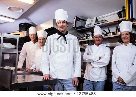 Portrait of happy chefs team standing together in commercial kitchen