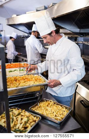 Chef standing at serving trays of pasta in commercial kitchen