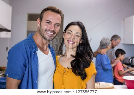 Portrait of happy young man and young woman standing in kitchen