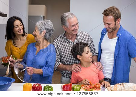 Portrait of happy family in the kitchen chopping vegetables at home