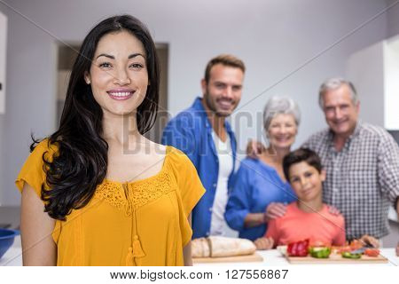 Portrait of beautiful young woman in the kitchen and other family member standing in background