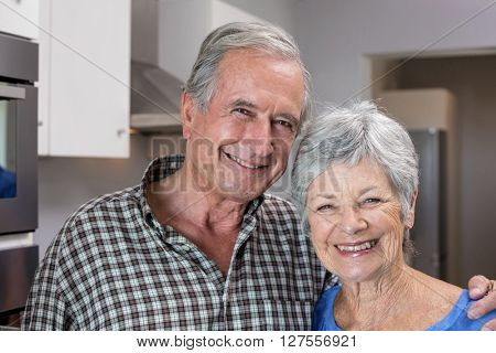 Portrait of elderly man and woman standing in the kitchen