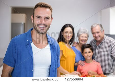 Portrait of handsome young man in the kitchen and other family member standing in background