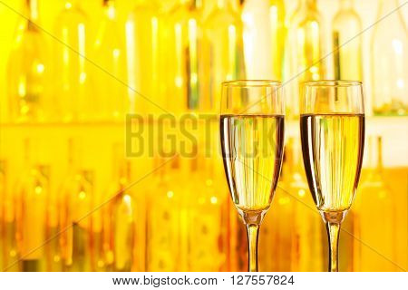 Glasses of champagne standing on bar counter at yellow lights