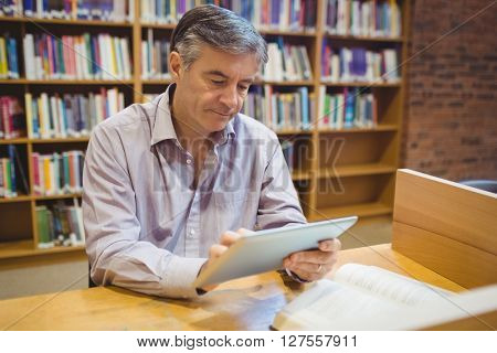 Professor sitting at desk using digital tablet in college library