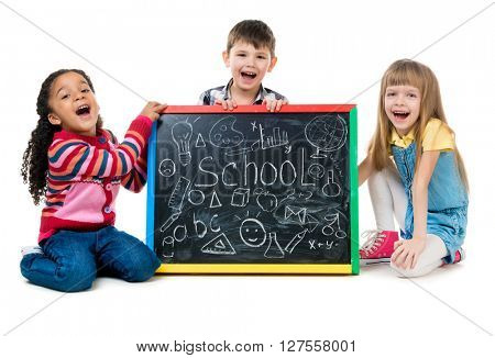 tree cheildren look at little blackboard sitting on the floor isolated on white background