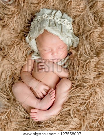 newborn bare baby in hat sleeping on fluffy blanket