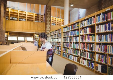 Young student using his laptop in college library