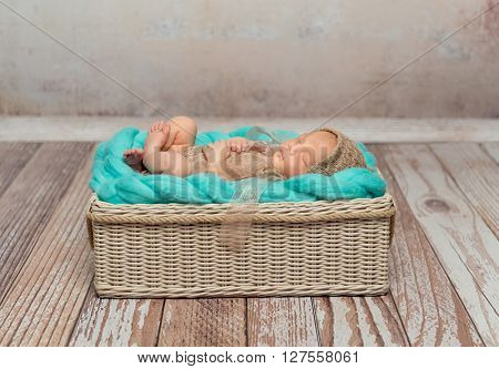 cute newborn baby in costume on turquoise blanket in cot