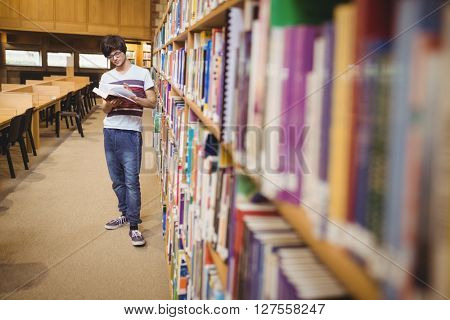 Young student reading book while standing near bookshelf in college library