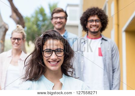Portrait of happy young woman with her friends in background
