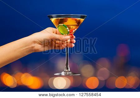 Hand with full martini glass with two chips inside in front of city skyline bokeh