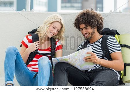 Young couple sitting on terrace and looking at map