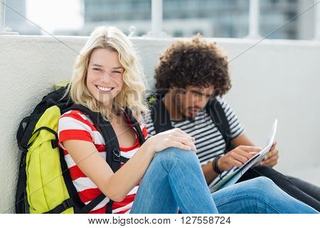 Beautiful woman smiling at camera while man looking at map on the terrace