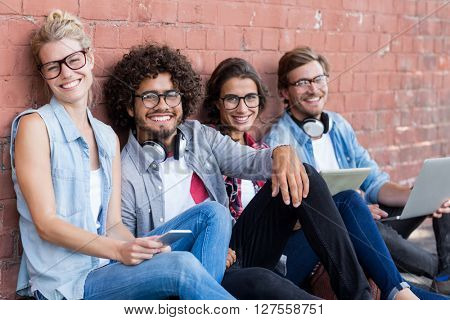 Portrait of friends sitting against wall using mobile phone, digital tablet and laptop