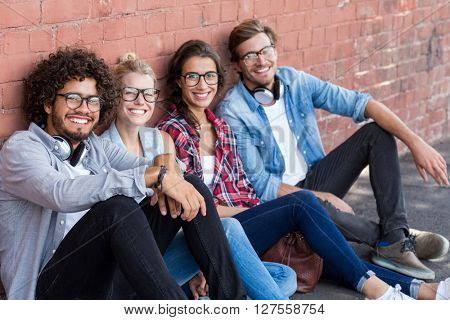 Portrait of happy friends sitting against wall