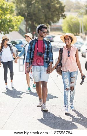Happy young couple walking hand in hand on road