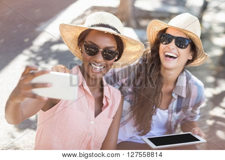 Friends in sunglasses taking selfie on a mobile phone