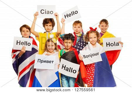 Kids wrapped in flags of USA and European nations, holding greeting signs in different languages, isolated on white