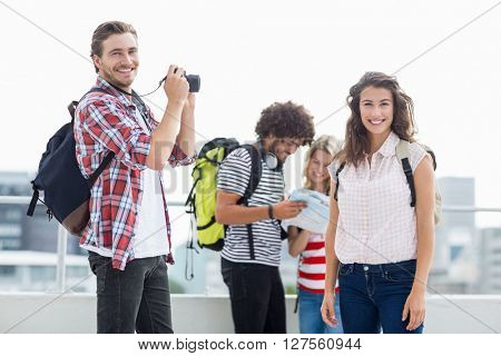 Young man taking photo of woman while friends interacting in background