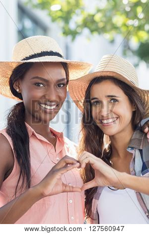Portrait of happy friends making heart shape with hands