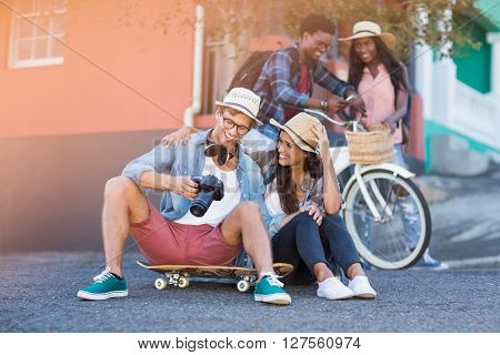 Couple sitting on road interacting while their friends standing in background
