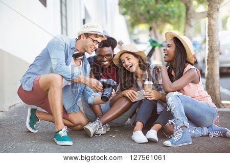 Man showing photos in camera to his friends outdoors