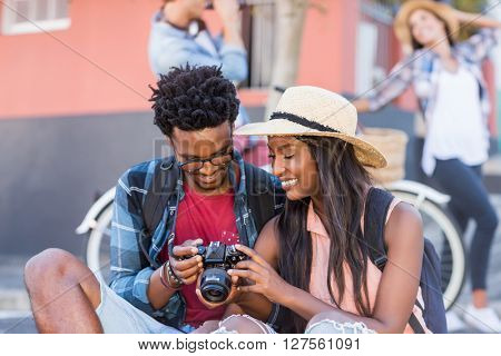 Happy young couple sitting on road looking in camera
