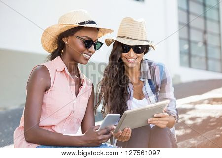 Young women in sunglasses using digital tablet and mobile phone