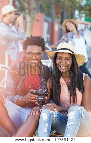 Portrait of happy young couple holding camera