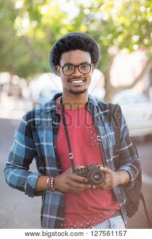 Portrait of young man holding camera outdoors