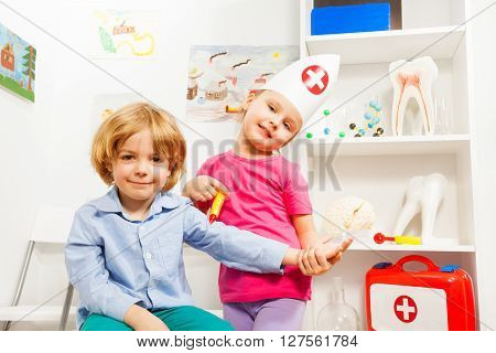 Little girl at medical cap playing a doctor doing injection to her patient at the clinic