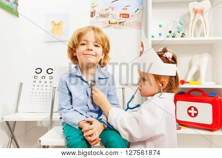 Little girl dressed like a doctor examining boy with stethoscope at the er