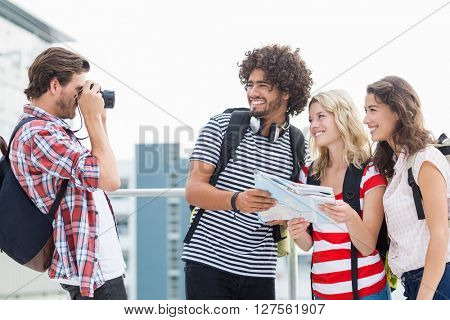 Man taking photo of his friends outdoors on terrace