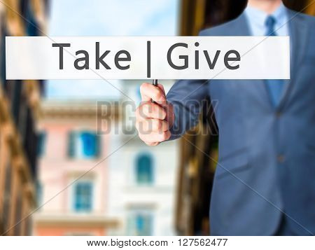 Give  Take - Businessman Hand Holding Sign