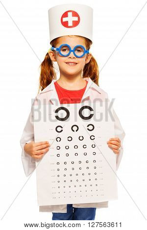 Little girl dressed as ophthalmologist, holding board for sight testing, isolated on white background