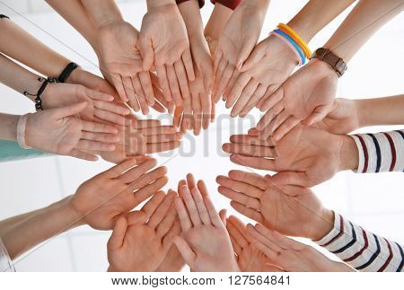 Group of people hands together, looking up view